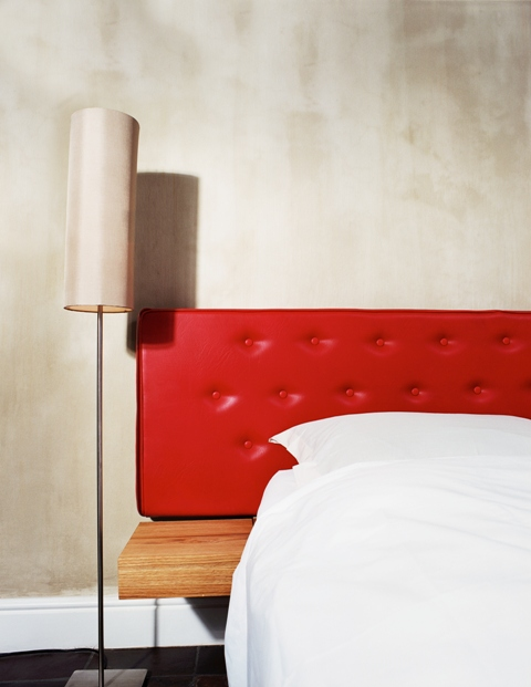 close-up of the side of a bed with a red leather headboard and a lamp beside it