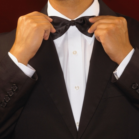 Man adjusting black bow tie